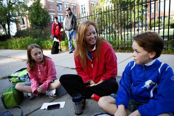 Liz Shirley waits with her children McClaran, 12, left, and Carter, 11, right, outside Alexander Graham Bell Elementary School for a bus to Lincoln Middle School on the first day back to school after the teachers strike.