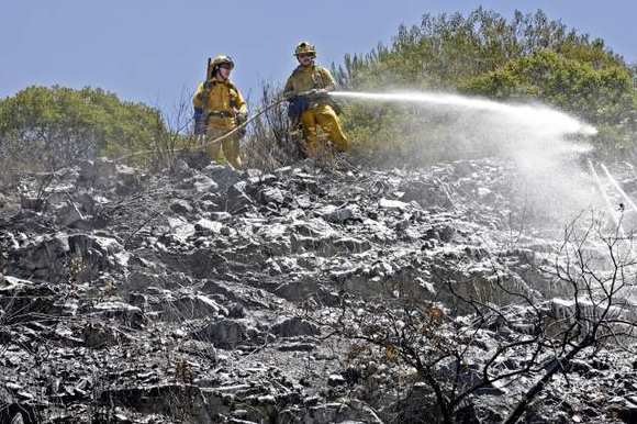 Firecrews hose down a hillside after a brushfire burned two acres on the northbound 2 freeway at Mountain Street on Friday, July 19, 2012.