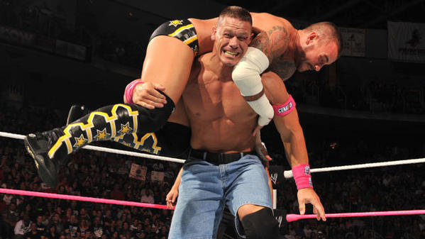 "John Cena hoists CM Punk into the air during ""Night of Champions."""