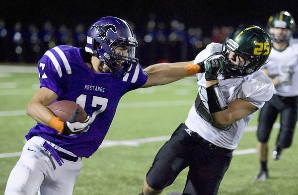 Jacob Grant of Rolling Meadows fights off Fremd defender Stephen Helbing