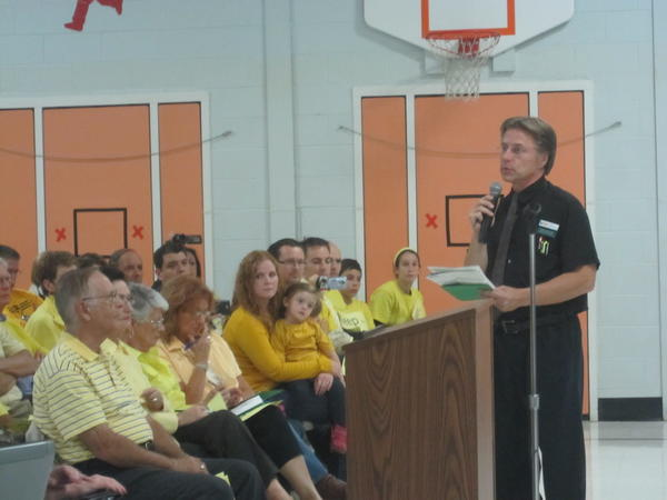 District 230 School Board President Frank Grabowski addresses residents during a special school board meeting called to discuss a possible change to attendance zones in the district. Residents opposed to losing an option zone that allows students to chose between Sandburg High School and Stagg High School wore yellow to the meeting.