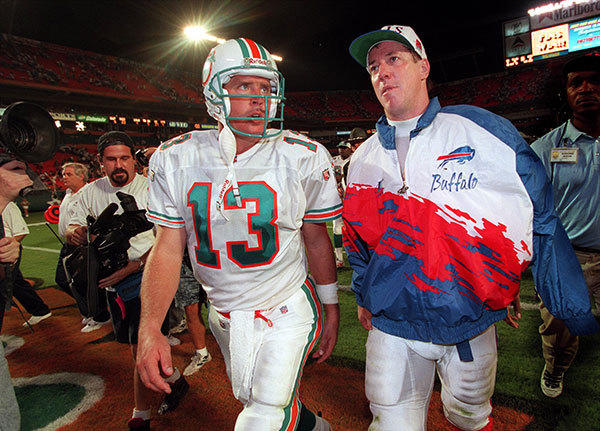 Dan Marino walks off the field with fellow QB Jim Kelly after a Monday night game vs Buffalo in Miami in 1999.