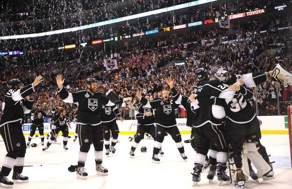 Los Angeles Kings players celebrate the Stanley Cup after defeating the N