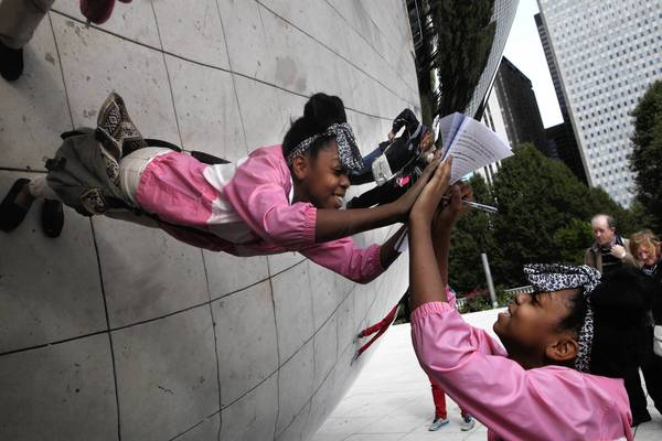 "Mia Bacon, 13, an 8th grade student at University of Chicago Charter School Woodlawn campus, works on a location writing assignment in Millennium Park at ""The Bean."" The children walked around downtown Chicago making observations and writing them into stories."