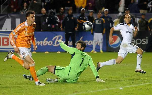 Galaxy midfielder Landon Donovan shoots the ball over Dynamo goalie Tally Hall to score the game-winning goal in the MLS Championship at the Home Depot Center in November. AEG owns both teams.
