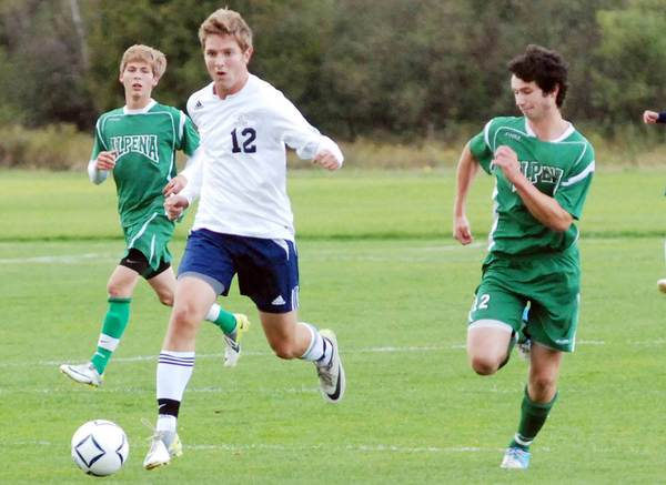 Petoskey senior Adam Bayer (12) pushes the ball upfield as Alpena senior Aaron Mead (right) gives chase during the first half of Tuesday's Big North Conference match at the Click Road Soccer Complex.