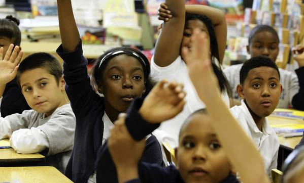 Fourth-graders raise their hands eager to answer questions on magnetism during the first day back to school at South Loop Elementary School. The students missed over a week of school due to the teachers strike.