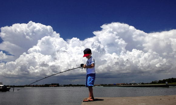 A young boy goes fishing in Ocean Ridge as clouds move in.
