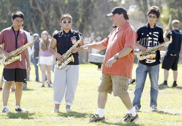 Huntington Beach High Band Director Gregg Gilboe demonstrates some footwork during drills on Friday.