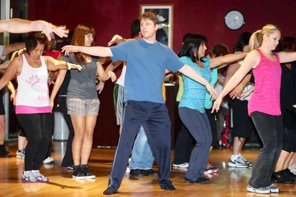 "Huntington Beach Independent City Editor Michael Miller, center, learns dance moves to Michael Jackson's ""Thriller"" at the Dance Asylum in Costa Mesa on Tuesday."
