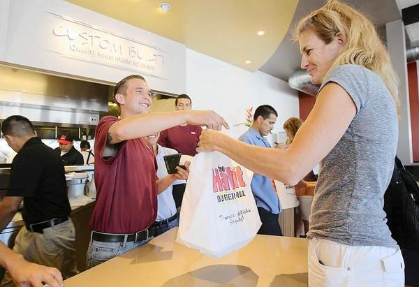 Benjamin Allen hands an order to Mika Mitchell at the Habit Burger Grill on Monday to benefit the Huntington Beach Education Foundation.