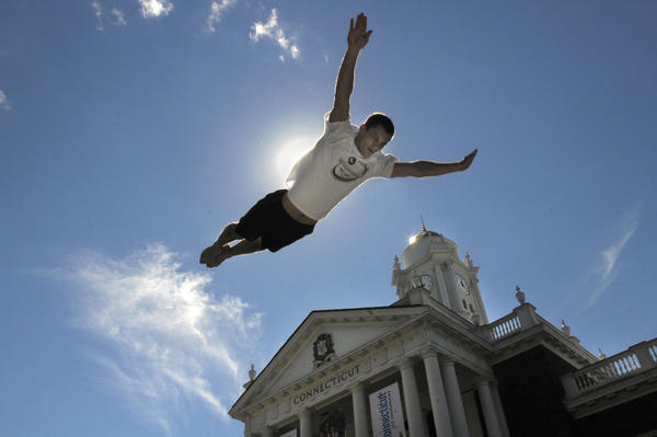 Sean Kennedy, who works and trains at the Trampoline Place in Plainfield Connecticut, performs for the crowd in front of the Connecticut building at the fair. Kennedy, of Holland Massachusetts, is a college student, and said he used to compete on the USA national team and still does shows.
