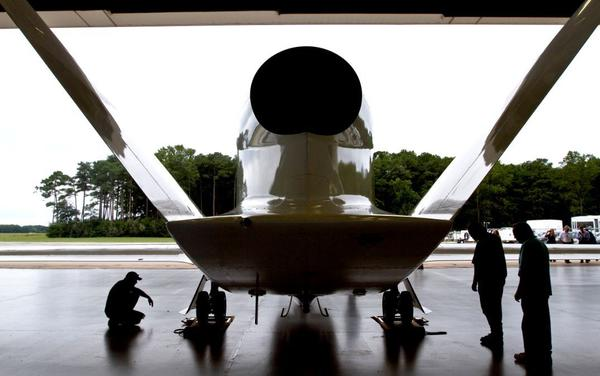 A ground crew checks over NASA's Global Hawk before its mission on Wednesday on Wallops Island. The unmanned aircraft takes readings and collects data on hurricanes and tropical storms from 60,000 feet in the air.
