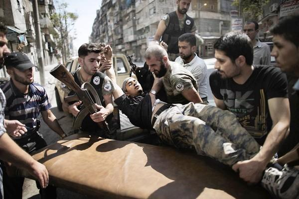 Rebels help a comrade wounded in a Syrian army strike in the northern city of Aleppo on Tuesday.