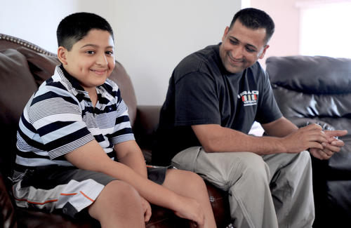 Toseef Mughal, 9, of South Whitehall, nearly died of sepsis 7 months ago.  Doctors amputated several fingers and parts of his feet to save his life.  He and his father, Shoukat Mughal, are in their home on Friday.