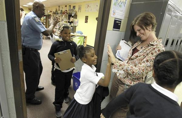 On the first day of classes after the teachers strike, librarian Lisa Martin-Eatinger and security officer David Finney high-five third graders Wednesday at South Loop Elementary School.