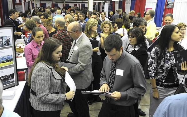 Sarah Hughes of Rexroth in Bethlehem talks to job seeker Josh Gmitter of Northampton on Wednesday at the Raymond E. Spencer Pennsylvania CareerLink Lehigh Valley Job Fair at Ag Hall at the Allentown Fairgrounds.