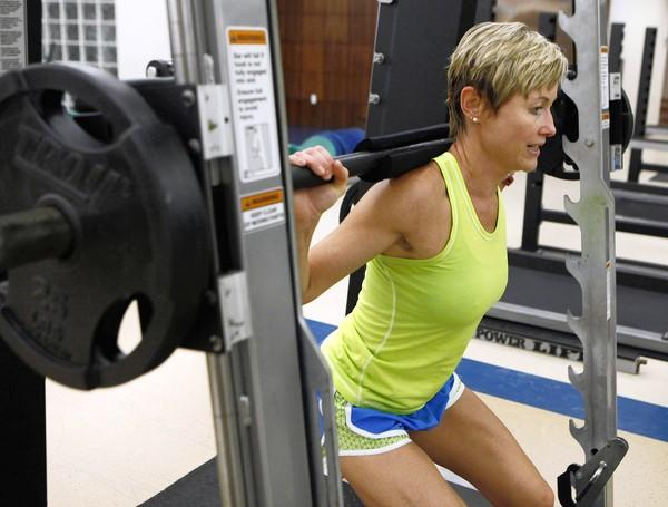 Gina Garcia, the assistant fitness director at SMU, does squats with a Smith Machine at SMU's Dedman Center in University Park, Texas, Wednesday, July 25, 2012.