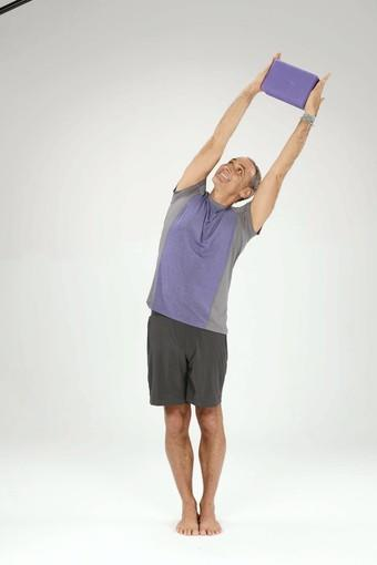 On an inhalation, firmly squeeze the block with both hands as you lean your torso to the left.