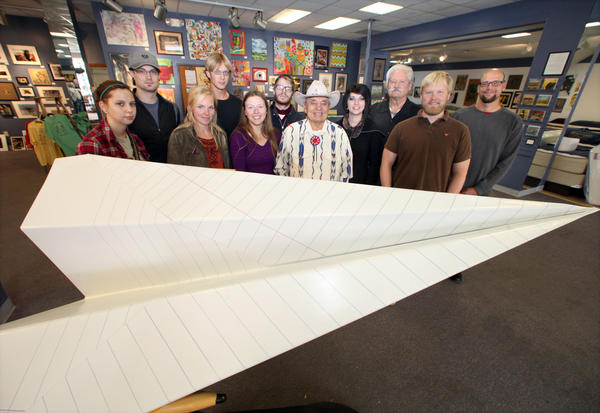 Artists gather around Matthew Freidel's salute to the paper airplane at Gallery Go on Main. From left are Megan Schaefer, Freidel, Nicole Fischer, Nick Fischer, Linda Roesch, Jeremy Burckhard, Vic Runnels, Amanda Barry, James Johnson, Mattress Matters owner Jason Hepola and Aaron Bigelow.