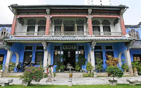 Tourists walk in front of Cheong Fatt Tze Mansion in Georgetown in Malaysia's northern state of Penang