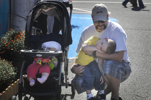 "It was Connecticut Day at the Eastern States Exposition, or ""Big E,"" Wednesday. Chris Durham, of Winsted, holds his three-year-old son Andrew in his arms, as his six-month-old daughter, Ashley relaxes in her carriage. Durham said his family comes to the fair every year on Connecticut day."