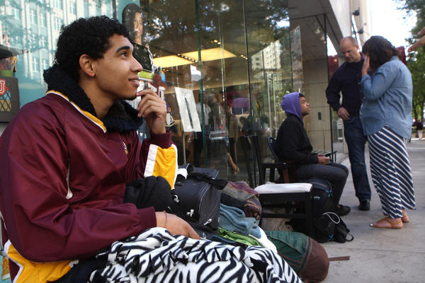 Devin Torkelsen, 19, of Chicago, waits to buy an iPhone 5 Thursday in front of the Apple Store on North Michigan Avenue in Chicago along with Ahmad Saleem, 24, 2nd from left, of Chicago, who chats with Apple employees Duke Zurek and Brooke Schulze. Torkelsen and Saleem have been waiting since Tuesday in front of the store.