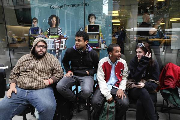 Charles Bahmandeji, 24, left, Ahmad Saleem, 24, Gregory Thornton, 23, all from Chicago, and Danielle Dietze, 22, of Evanston, wait Thursday in front of the Apple Store on North Michigan Avenue in Chicago where they have been waiting for days to purchase the iPhone 5 when it goes on sale Friday.