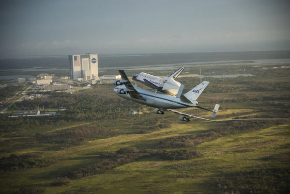 Space Shuttle Endeavour is ferried by NASA's Shuttle Carrier Aircraft (SCA) over the Kennedy Space Center in the early morning hours of September 19, 2012 as it departs for California.