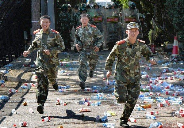Paramilitary police run past bottles thrown by demonstrators outside the Japanese Embassy in Beijing this week.