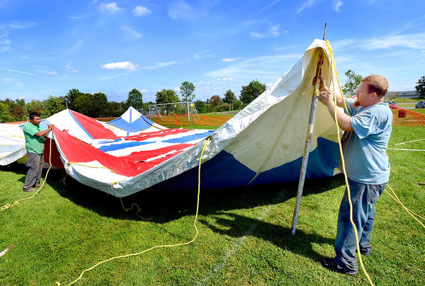 Pete Martinez, left, and his supervisor Kevin Waltrip, right, of Weiser Tent Service in Monett, Mo., set up tents all day Thursday preparing for Saturday's Convoy Of Hope at Hagerstown Fairgrounds Park.