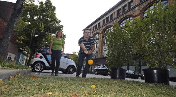 Members of Floura Teeter landscape architecture firm play bocce in parking spaces taken over for a day on West. Franklin Street.