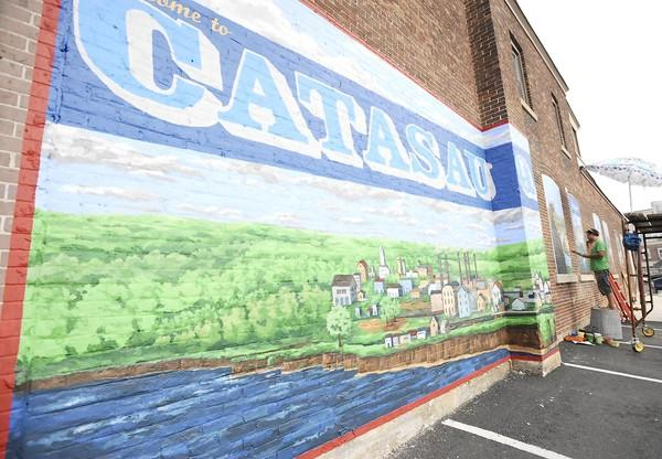 Chris Kosztyo, of Bethlehem, helps paint a mural on the wall of 117 Pine Street in Catasauqua on Friday.