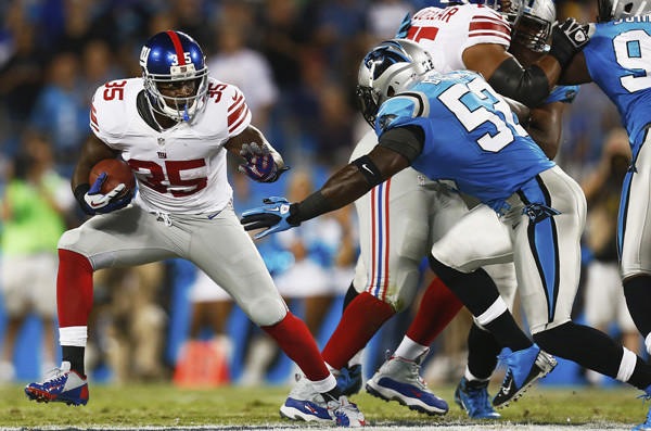 New York Giants running back Andre Brown runs the ball against Carolina Panthers middle linebacker Jon Beason during an NFL football game in Charlotte. (Reuters)