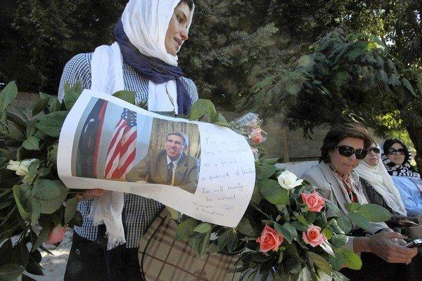 A Libyan woman carries a wreath bearing slain U.S. Ambassador J. Christopher Stevens' picture in Benghazi. Stevens and three other Americans died in an attack on the U.S. Consulate last week.
