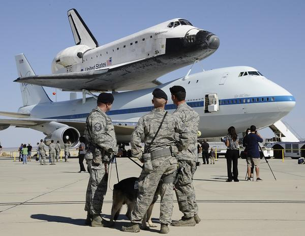 Military personnel look at the Shuttle Carrier Aircraft (SCA) modified 747 aircraft and the space shuttle Endeavour at the Dryden Flight Research Center.