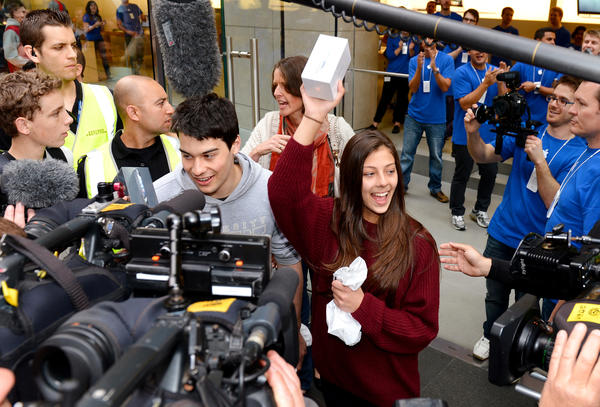 James (centre-L) and Tamsyn Vohradsky (centre-R) hold up their iPhone 5 after becoming the first buyer of Apple's new iPhone 5 from their flagship store in Sydney, on September 21, 2012. Gadget lovers in Australia were the first to get their hands on the new generation iPhone 5, with the queues snaking around Apple's flagship store in Sydney suggesting another huge hit for the company.