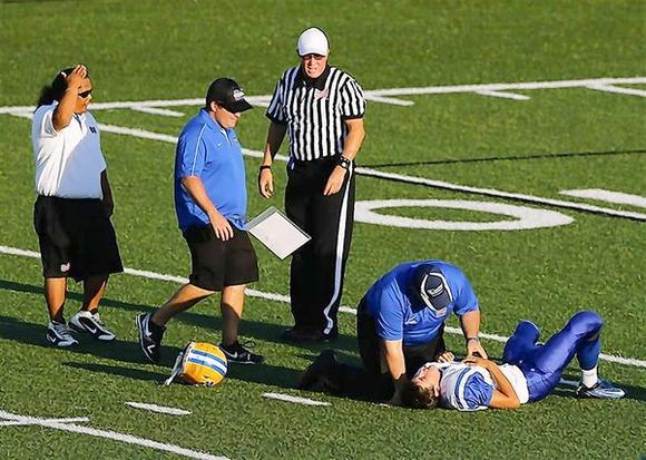 A Mira Mesa junior varsity high school football player is attended to by training staff after being hit by an Oceanside Pirates player during their game in Oceanside