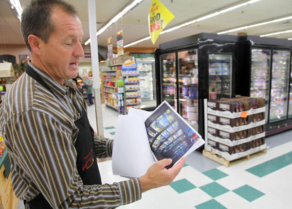 Kevin Fiedler, the general manager at Ken's SuperFair Foods, talks about the new energy-saving lighting system, including LED lighting in the freezer cabinets, at the Aberdeen grocery store.