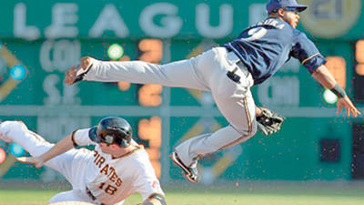 Milwaukee Brewers shortstop Jean Segura (9) leaps over Pittsburgh Pirates' Neil Walker (18) to turn a second-inning double play on Pirates' Pedro Alvarez at first base during a baseball game in Pittsburgh, Thursday.