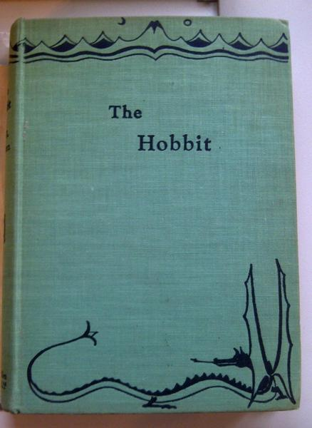 "Under the dust jacket of the first edition of ""The Hobbit,"" the cover is decorated with a drawing by J.R.R. Tolkien."