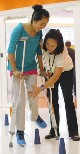 "Physical therapist Nicole Williams works with Sajina Tamang, left, at the Rehabilitation Institute of Chicago. Forced into slavery by an overseas ""employer,"" Tamang was routinely beaten, and eventually incapacitated after being thrown from a fifth-floor balcony. Following free surgery from humanitarian group Operation Walk's Chicago chapter, she has begun to walk unassisted for the first time in years."