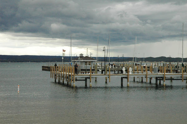A sheet of rain moves over the Petoskey area behind anglers fishing from the docks at Petoskey's waterfront.
