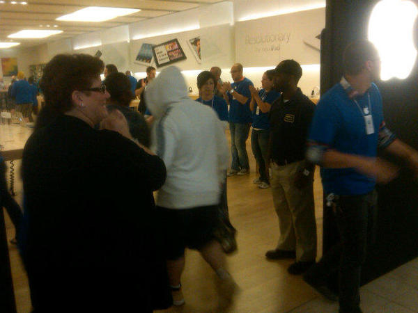 Employees clap as the first customers enter the Westfarms Apple Store to pick up their new iPhones.