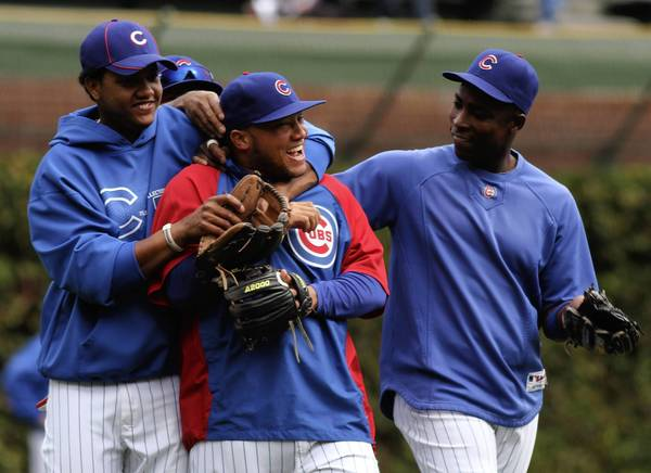 Starlin Castro, left, and Alfonso Soriano, right, joke with catcher Wellington Castillo during warm-ups before the Chicago Cubs vs. St. Louis Cardinals game at Wrigley Field in Chicago.