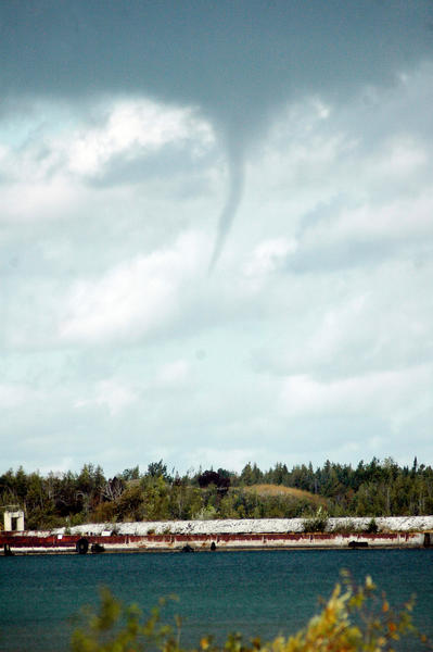A funnel cloud descends from the sky over Lake Michigan just off shore from the St. Mary's Cement plant dock near Charlevoix today, Friday, Sept. 21.