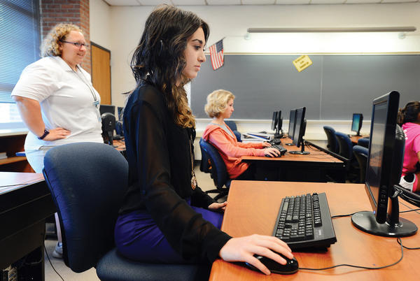 Smithsburg High School student athlete Morgan Thorhauer, front, takes her computer-based memory test while certified athletic trainer Ryann Frye, left, looks on. At rear, is fellow student athlete Samantha Tilden.