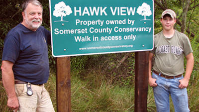 Jim Moses, left, president of the Somerset County Conservancy and Logan Lichvar stand with one of the new conservancy signs.