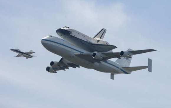 The space shuttle Endeavour is photographed by many as it flies over Mt. Hollywood and the Griffith Observatory in Los Angeles on Friday, Sept. 21, 2012.