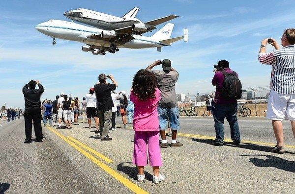 Spectators line Aviation Boulevard as the space shuttle Endeavour, atop its 747 transport, nears the runway at Los Angeles International Airport.
